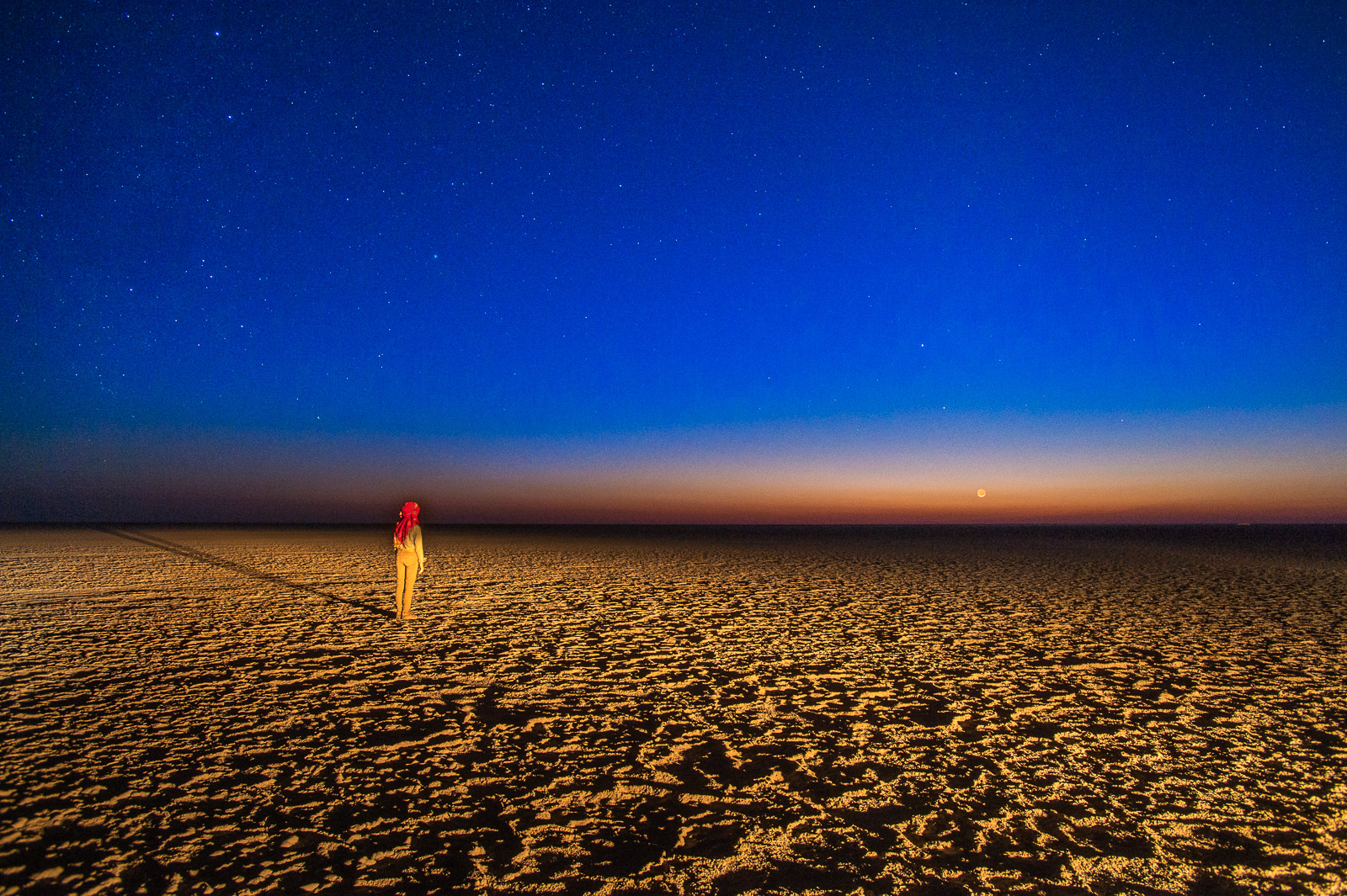 Woman watching evening sky, Makgadigadi Pan, Botswana