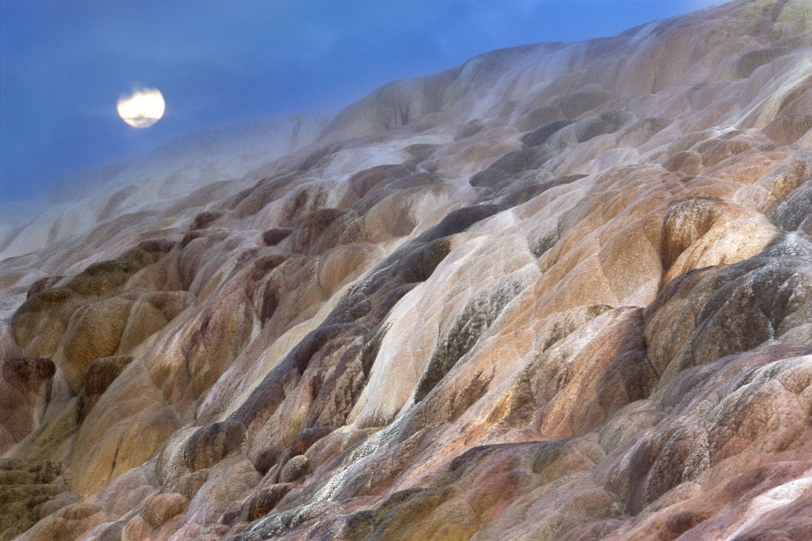 Moonrise over mineral terraces, Yellowstone National Park, Wyoming, USA